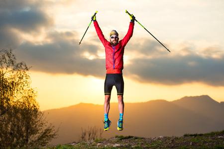 Sport man maakt een sprong in de bergen tijdens een zonsondergang.