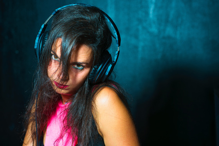 Pretty expressive girl deejay with headphones on her console at a party or night club.