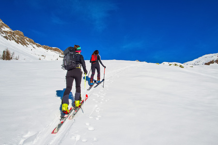 Ski mountaineering two girl uphill towards a mountain. 스톡 콘텐츠