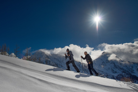 Snowshoes practiced by a boy and a girl in the warm mountain sun.