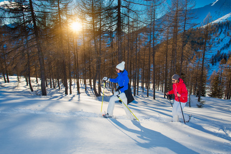 Couple of girlfriends walk with snowshoes at sunset. Banco de Imagens