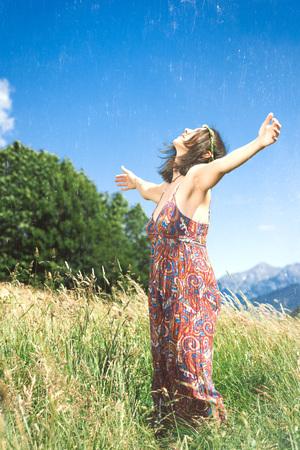 Girl meditates alone in a hillside meadow. Stock fotó