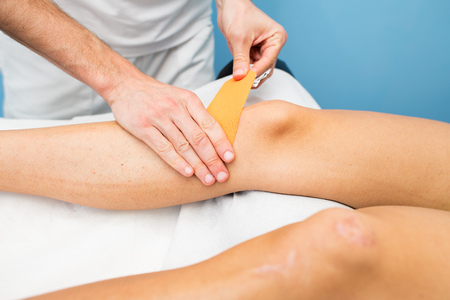 Kinesio taping knee application of a physiotherapist.