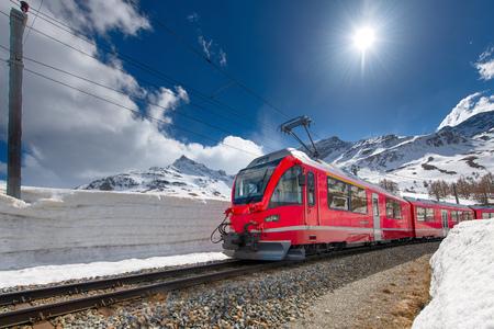 Swiss mountain train Bernina Express crossed Alps with snow wall. Redakční