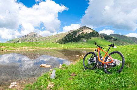 Mountain ebike stops near an alpine lake in spring.