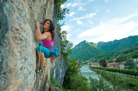 Girl practicing free climbing on rock with panorama of the village.