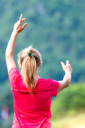 A blonde woman practices tai chi chuan at the park. Stock Photo