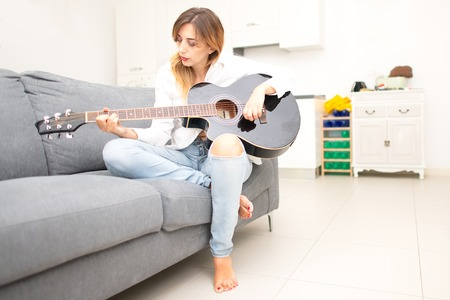 Beautiful woman plays her guitar on the sofa at home after work in the office.