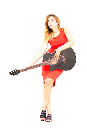 Woman dressed in red with guitar in hand on white background.