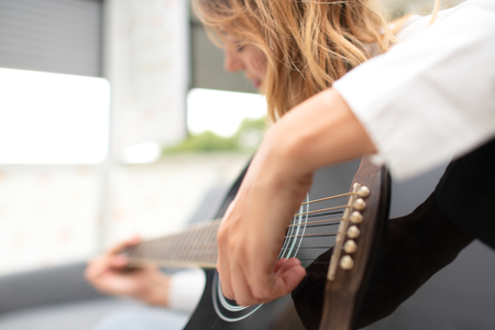 Woman plays her left-handed guitar at home after work in the office.