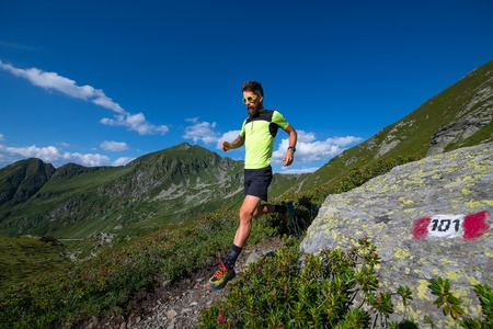 Male athlete practicing mountain running on a trail downhill.