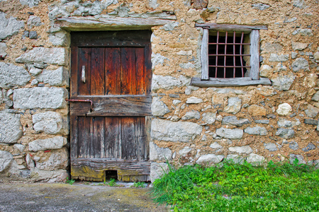 Ancient wooden door with window railing in the house of pebbles of an ancient border. Imagens - 111371630