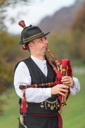 Typical player in traditional northern Italy bagpipe costume, an alpine valley of Bergamo.
