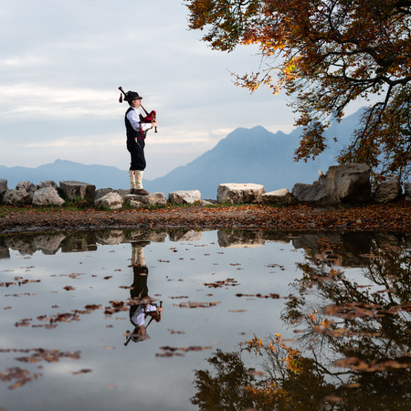 Bergamo player Bagpipe is reflected in a pool of water.