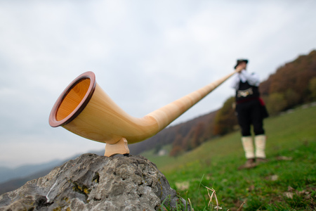 Alpine horn. A man plays in an alpine valley.