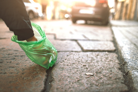 Person collects with bag of dog droppings in the city.
