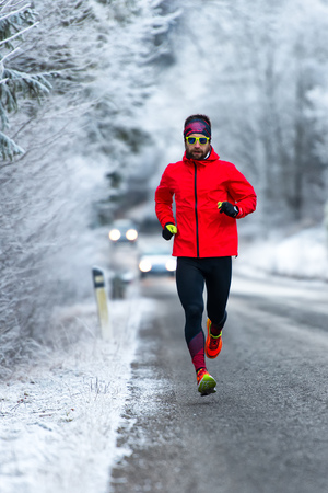 Man during a workout on icy road in winter. Stock Photo