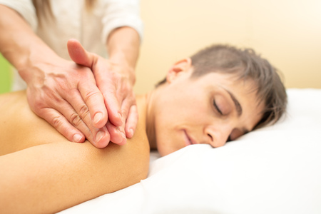 Beautician practices a relaxing aesthetic massage behind a young woman. Stock Photo