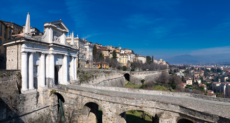 Bergamo. Porta San Giacomo with the walls that divide the upper city from the lower. Stock Photo