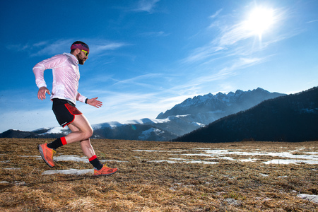 Mountain runner in downhill action on slippery ground