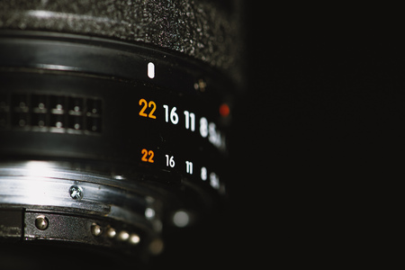 Camera lens with aperture numbers on a black background Stock Photo