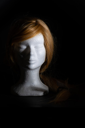 Blonde wig on a polystyrene head on a black background