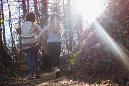 Little girls are walking on the mountain path during a trip with little excursionists Stock Photo