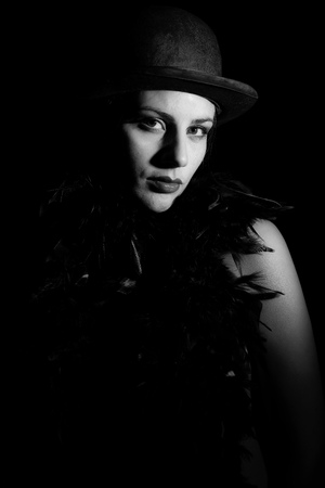 Portrait of woman in bowler hat on black background in black and white