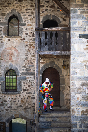 ONETA, BERGAMO, ITALY - MARCH - 30 - 2019:The mask of Arlecchino. On the stairs of the house Editorial