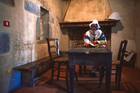The mask of Arlecchino. Sitting on the table of an old house Editorial