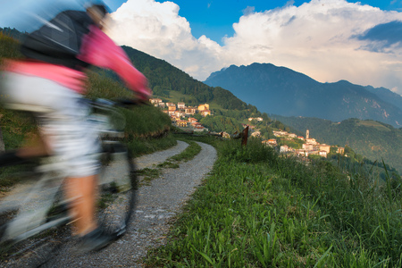 Blur effect of a mountain bike on a dirt road towards the small mountain village Stock Photo