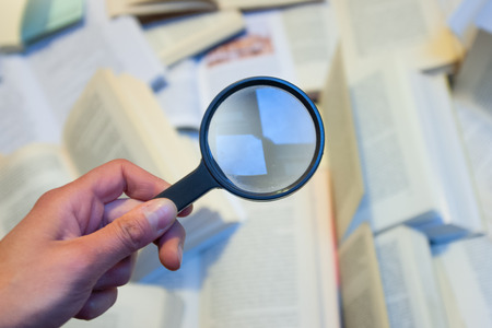 Magnifying glass to check various books
