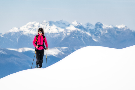 Young woman on ridge of so much snow rises towards the top in the mountains