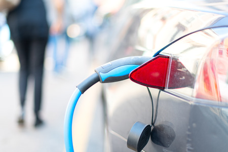 An electric car is charged with energy by a road dispenser Stock fotó