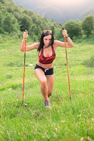 Frau klettert mit Stöcken steilen Bergpfad