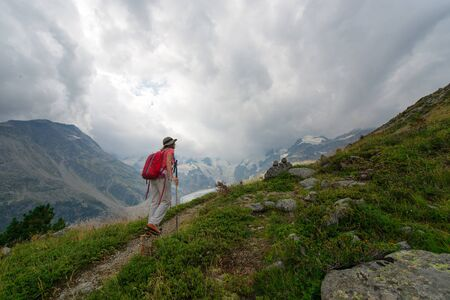 Retired woman practices a hike in the high mountains