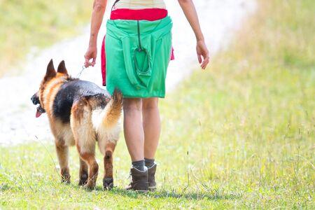 Dettaglio di una donna con il suo cane pastore tedesco durante un'escursione in montagna Archivio Fotografico