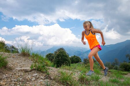 A girl practice running on trail in the mountains Reklamní fotografie