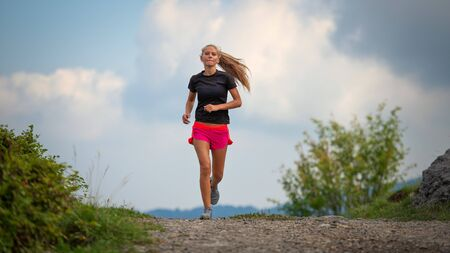 Young girl with lean physique running on hill dirt