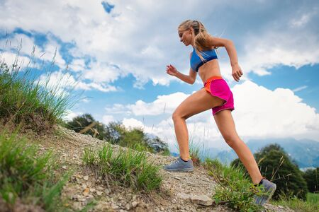 Young blonde girl athlete running in the mountains uphill on trail