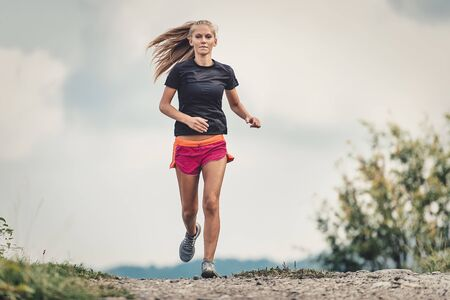 Beautiful blonde athlete runs on dirt road in the hills Reklamní fotografie