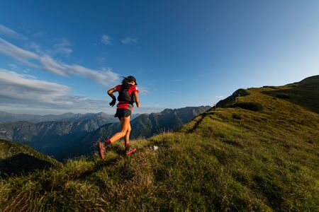 Sporty mountain woman rides in trail during endurance trail Imagens