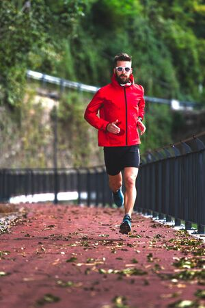 An athlete runs on the bike path in the fall