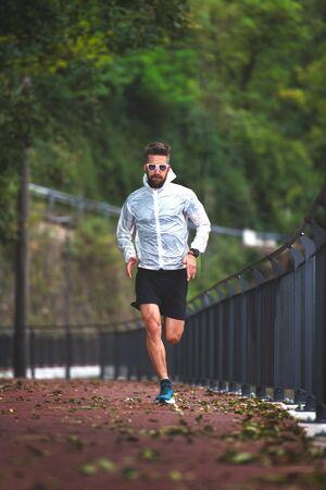 Runner on bike path in autumn trains Imagens