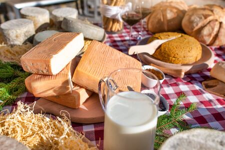 Milk and cheese with food on a table outside a farmhouse in the Italian Alps