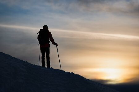 A mountaineer skier watches the sun go down