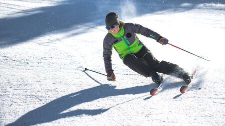 Carving curve of a girl ski instructor