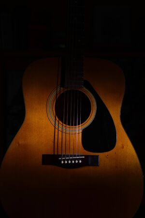 Close-up of an acoustic guitar on a black background between light or shadows Stock Photo