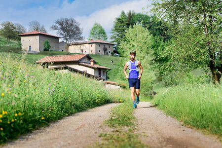Young athlete runs in rural hill landscape