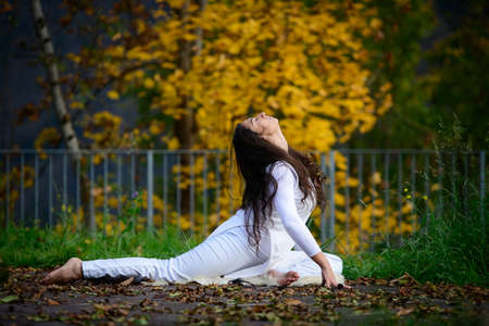 Woman in white in autumn park while doing yoga